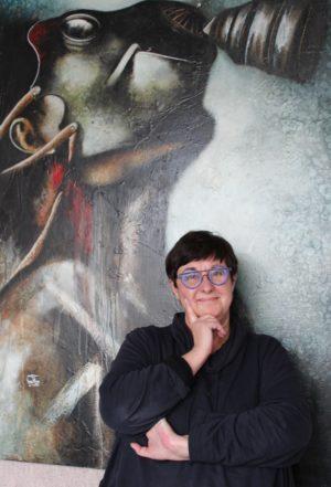 Christine Martin devant une peinture de Titus (crédits : Morgane Macé / Profession Spectacle)